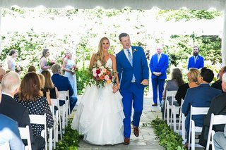 bride-and-groom-recessional-outdoor-wedding-stone-aisle-greenery-blue-suit-pink-bouquet