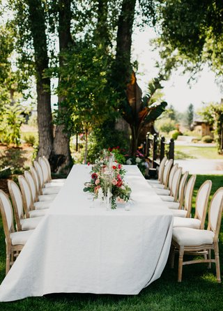 wedding-reception-inspiration-long-table-low-centerpiece-garden-style-wood-upholstery-chairs-trees