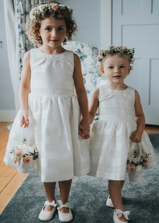 two-flower-girls-in-white-sleeveless-dresses-flower-crowns-baskets-with-pink-roses-white-bow-shoes