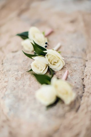 three-groomsmen-boutonnieres-with-two-white-rose-flowers-each-and-pink-ribbon