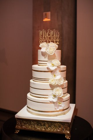 four-tiered-wedding-cake-with-gold-stripes-and-sugar-flowers-of-roses-and-orchids