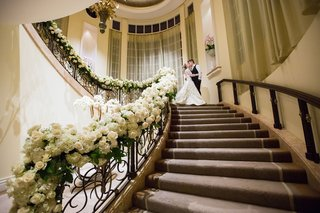 bride-and-groom-portrait-on-stairs-to-ballroom-at-beverly-hills-hotel-white-rose-hydrangea-greenery