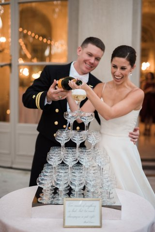 bride-and-groom-pouring-champagne-into-tower-of-glasses-coupe-glass-military-wedding-reception