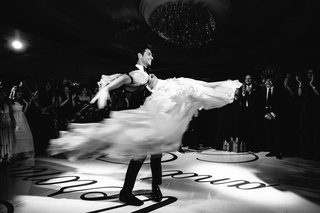 black-and-white-photo-of-bride-and-groom-performing-first-dance-at-wedding-on-custom-dance-floor