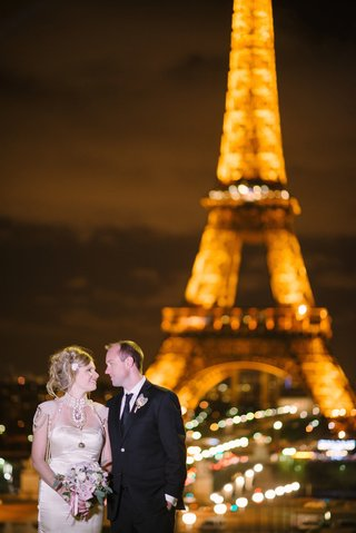 bride-in-satin-melany-rowe-dress-with-pearls-and-groom-in-tuxedo-by-the-eiffel-tower-in-paris