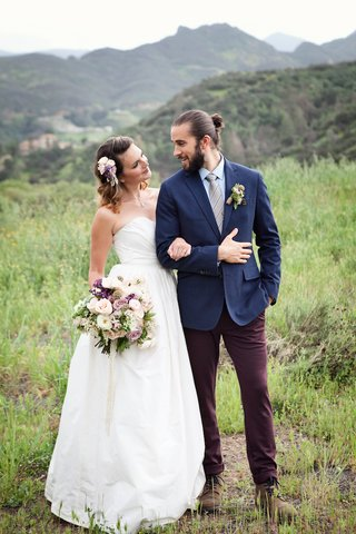 bride-in-a-strapless-ball-gown-and-groom-with-mun-man-bun-in-blue-blazer-brown-pants