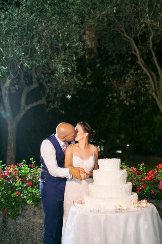 outdoor-wedding-cake-four-layer-pretty-traditional-confection-bride-and-groom-kiss-as-they-cut-cake
