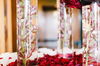 wedding-reception-place-card-table-with-red-flower-petals-and-pink-orchid-stems-in-cylinder-vases