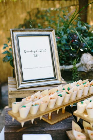 sweet-and-spicy-cocktail-nuts-in-bamboo-cones-in-wooden-stands-with-frame-menu-design-outdoor-weddin
