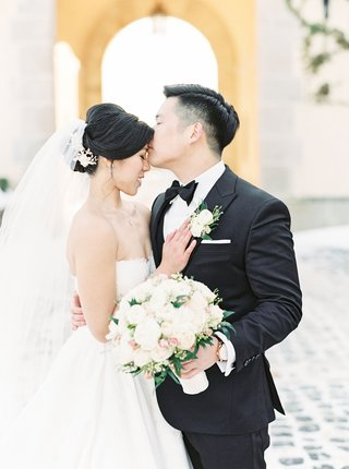 chinese-american-couple-kiss-forehead-oheka-castle-wedding-winter-snow-on-ground-strapless-dress