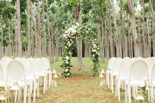 forest-wedding-ceremony-green-arch-neutral-flowers-white-chairs-and-lanterns-on-aisle