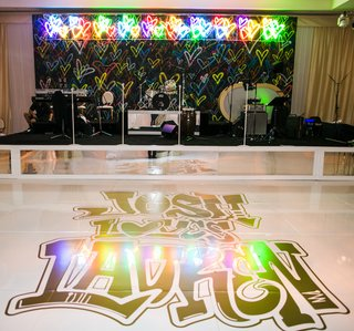 wedding-reception-modern-band-backdrop-colorful-hearts-neon-sign-graffiti-lettering-on-dance-floor
