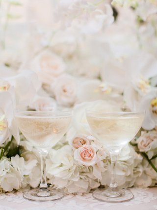 wedding-reception-etched-coupe-glass-for-champagne-at-wedding-reception-with-flowers-blush-ivory