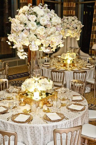 white-table-linens-with-details-gold-charger-plates-mirrored-stands-glass-vases-white-rose-flowers