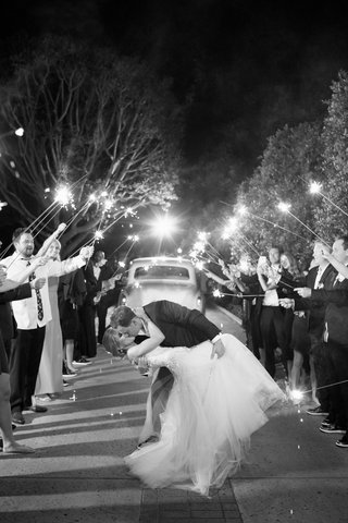black-and-white-photo-of-bride-being-dipped-by-groom-during-firework-sparkler-exit-getaway-car