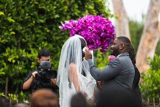 tall-bouquet-of-pink-flowers-next-to-couple-during-ceremony
