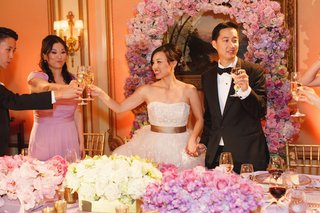 pink-and-white-flowers-decorate-head-table-and-wall-as-newlyweds-toast