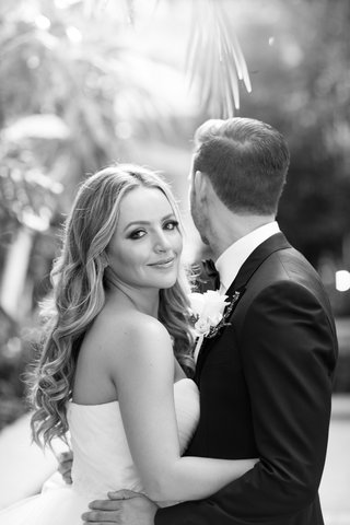 black-and-white-photo-of-bride-smiling-while-groom-looks-away