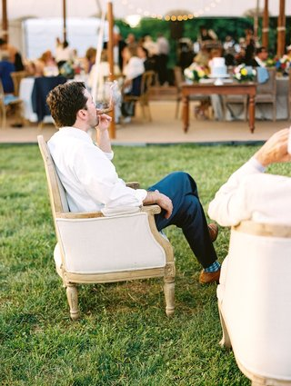 male-guest-having-cigar-at-cigar-station-lounge-area-by-tent-wedding-reception