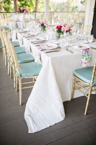 wedding-reception-on-porch-white-linen-sage-green-mint-cushions-gold-chairs-pink-pastel-centerpiece