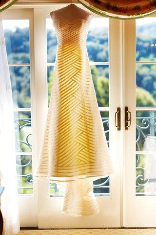 anne-barge-stripe-wedding-dress-hanging-in-front-of-door