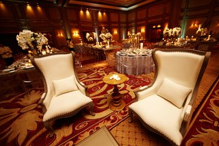 white-tall-back-arm-chairs-at-indoor-ballroom-reception