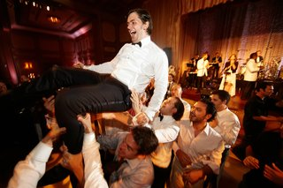 male-wedding-guests-lifting-groom-up-over-dance-floor