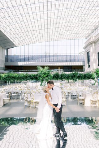 bride-and-groom-wearing-dress-shirt-without-jacket-kiss-on-mirror-dance-floor-before-guests-arrive