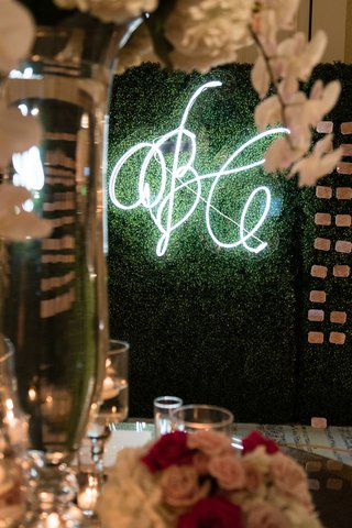 neon-sign-with-wedding-monogram-of-bride-and-groom-on-boxwood-wall-hedge-with-escort-cards-display