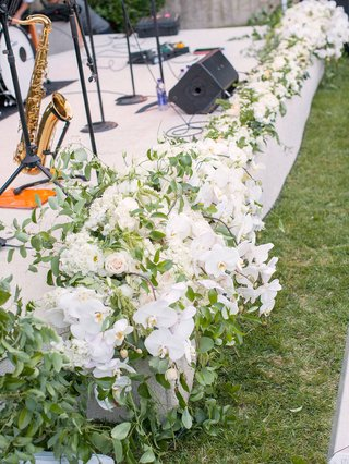 outdoor-white-stage-for-live-band-lined-with-cascading-white-orchids-and-greenery
