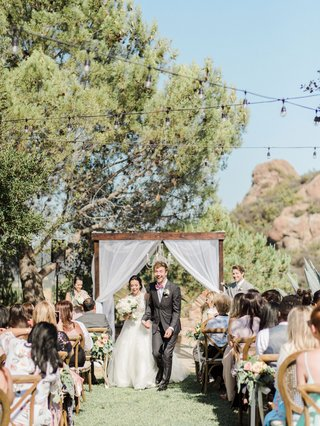 megan-nicole-flores-and-cooper-green-outdoor-daytime-wedding-ceremony-malibu-wood-arbor-guests