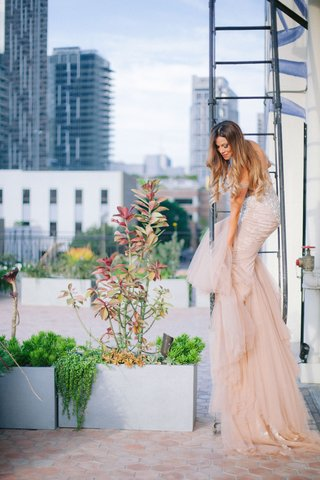 bride-on-fire-escape-staircase-downtown-los-angeles-wedding-venue-blush-inbal-dror-wedding-dress