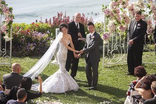 asian-bride-and-groom-hold-hands-at-oceanfront-ceremony