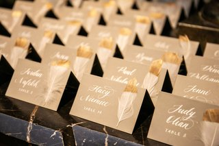 wedding-reception-escort-card-white-calligraphy-white-feather-dipped-in-gold-paint-on-marble-table