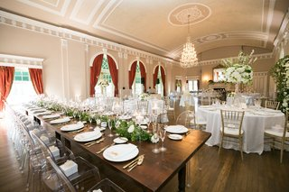 wedding-reception-ballroom-wood-floor-red-drapes-chandelier-wood-table-white-linens-greenery-white