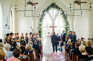 wedding-ceremony-bride-and-groom-altar-cross-arch-window-greenery-flower-petals-wood-floor-pews