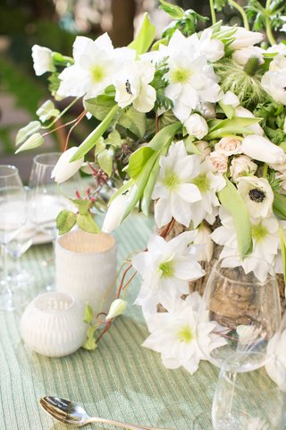 green-and-white-anemone-floral-arrangement-centerpiece-with-tree-stump-vase-and-small-white-candles