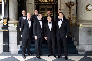 groom-and-groomsmen-in-tuxedos-bow-ties-leather-dress-shoes-checker-floor-hotel
