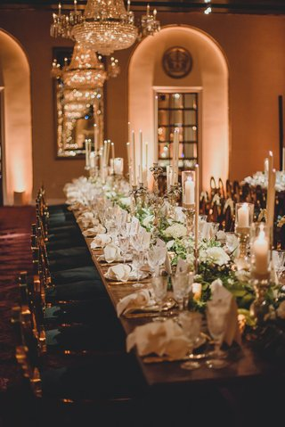 wedding-reception-long-table-green-gold-chairs-taper-candles-chandelier-white-flowers-greenery-luxe