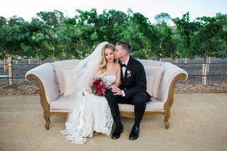 bride-and-groom-sit-on-white-and-gold-couch-on-vineyard-with-red-and-purple-bouquet