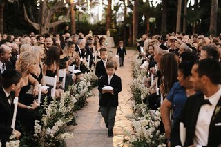 guests-looking-at-cute-ring-bearers-walking-down-stone-aisle-ring-pillow-stripe-tie