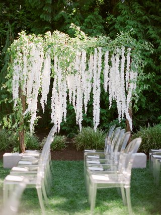 brandin-cooks-backyard-wedding-arbor-with-greenery-and-cascading-white-flowers-ghost-chairs