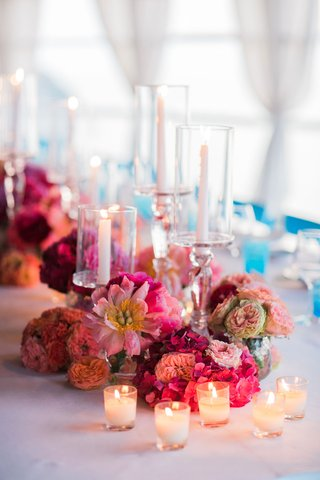 tea-lights-in-front-of-floral-centerpiece-with-bright-pink-and-peach-flowers