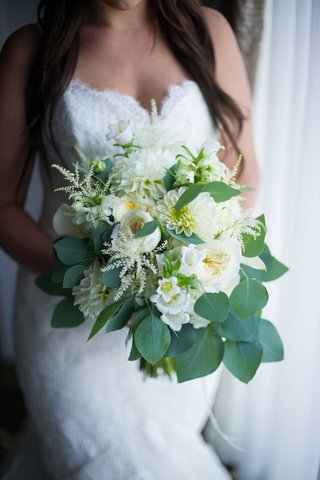a-bridal-bouquet-made-up-of-varying-white-flowers-and-leafy-green-foliage