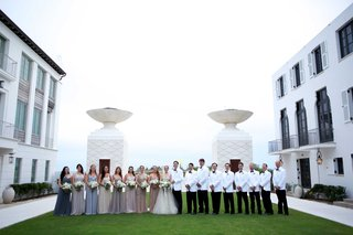 wedding-party-different-bridesmaid-dresses-white-suit-jackets-hotel-courtyard-ocean