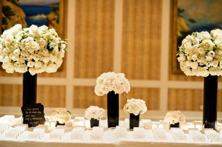 escort-card-setting-black-vases-white-flowers-white-escort-place-cards