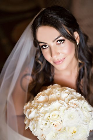 half-up-hairstyle-light-makeup-on-bride-holding-white-bouquet-of-flowers
