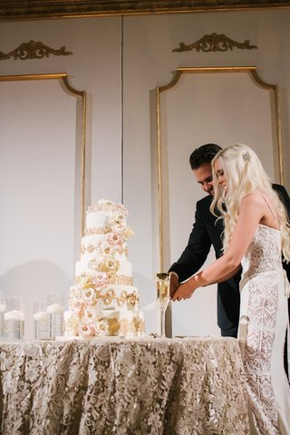 bride-in-a-galia-lahav-gown-with-lace-panels-cuts-cake-with-golden-details-sugar-flowers-with-groom