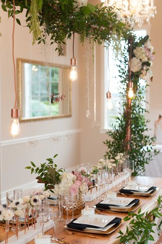 a-unique-modern-and-green-tablescape-head-table-with-hanging-lights-arch-copper-color-foliage