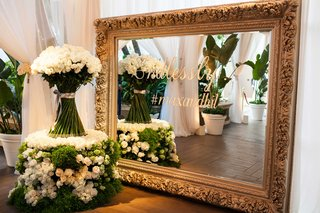 white-and-green-flower-table-with-white-rose-arrangement-gold-frame-with-wedding-hashtag-details